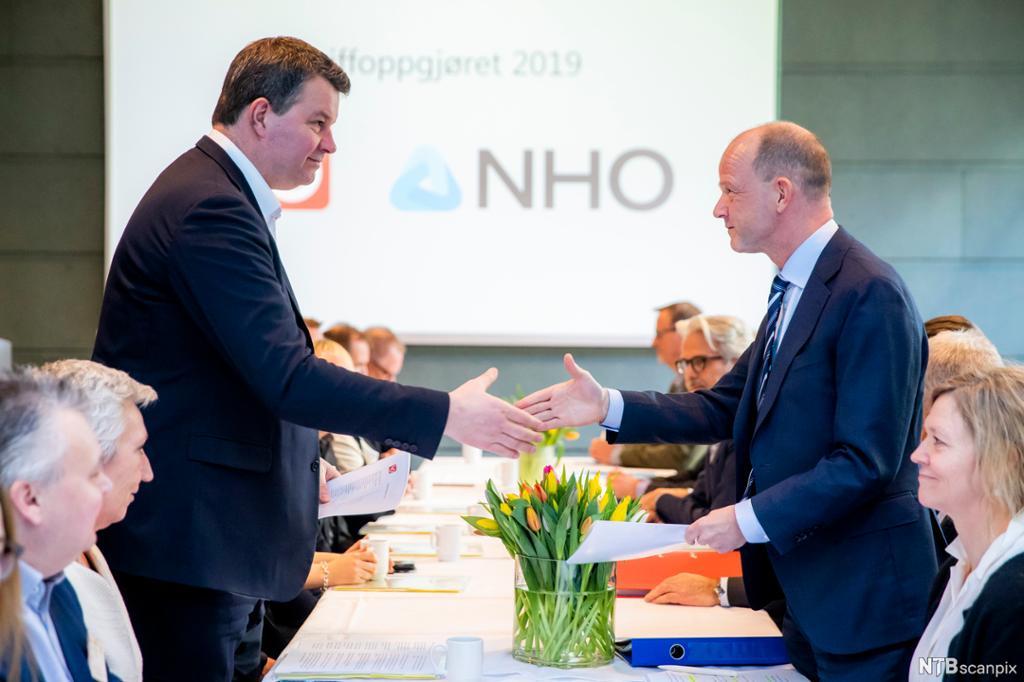 LOs leder og NHOs sjef hilser på hverandre fra hver sin side av bordet under åpningen av forhandlinger i 2019. Foto.
