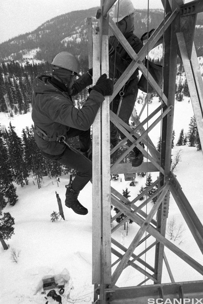 To mann med hjelm klatrer i mast.