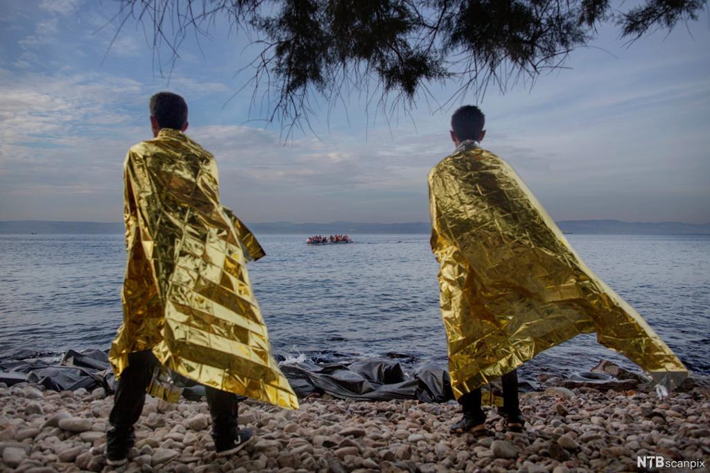 To menn forsøker å få tilbake varmen kledd i folier delt ut av frivillige.  Nå ser de to nye gummibåter med flyktninger ankomme øya. Foto.