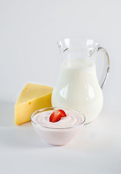 En mugge med melk, en skål med youghurt og litt ost. Foto.