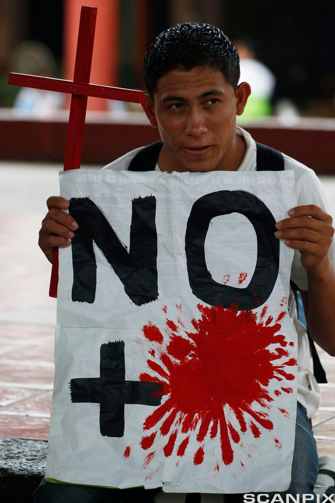 A Central American migrant, carrying a cross and a sign against violence, participates in a Via Crucis in Tapachula, Mexico, Wed
