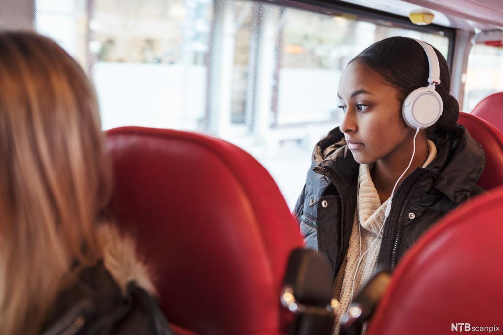 Ung jente med høretelefoner på bussen. Foto.