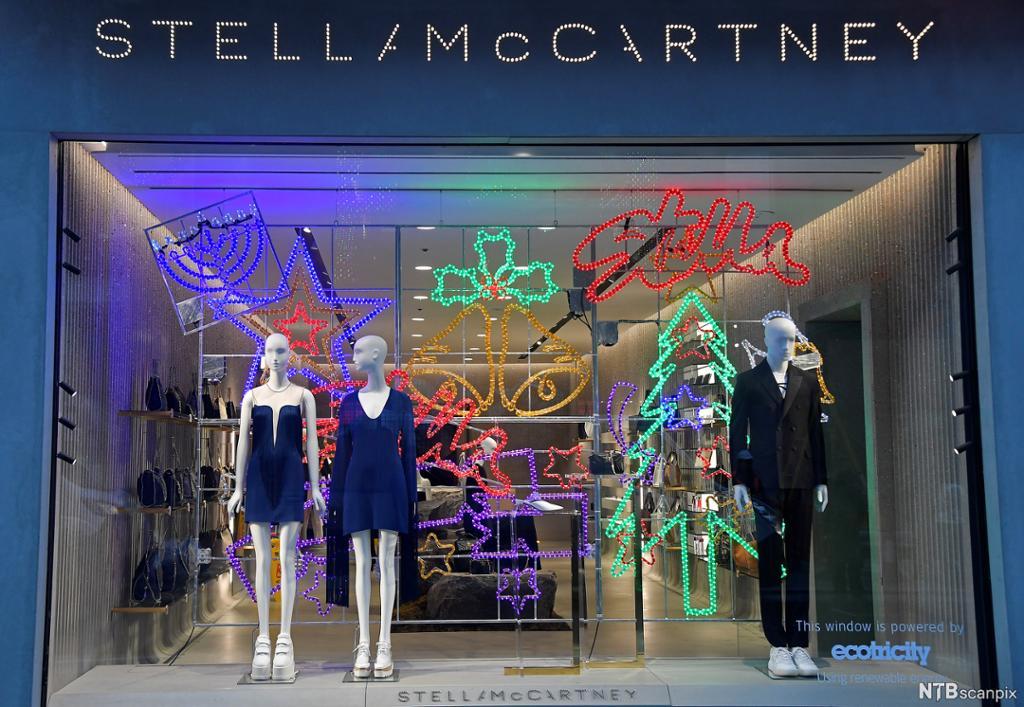 Utstillingsvindauge med kvite dukker i festantrekk, designa av Stella McCartney. Foto.