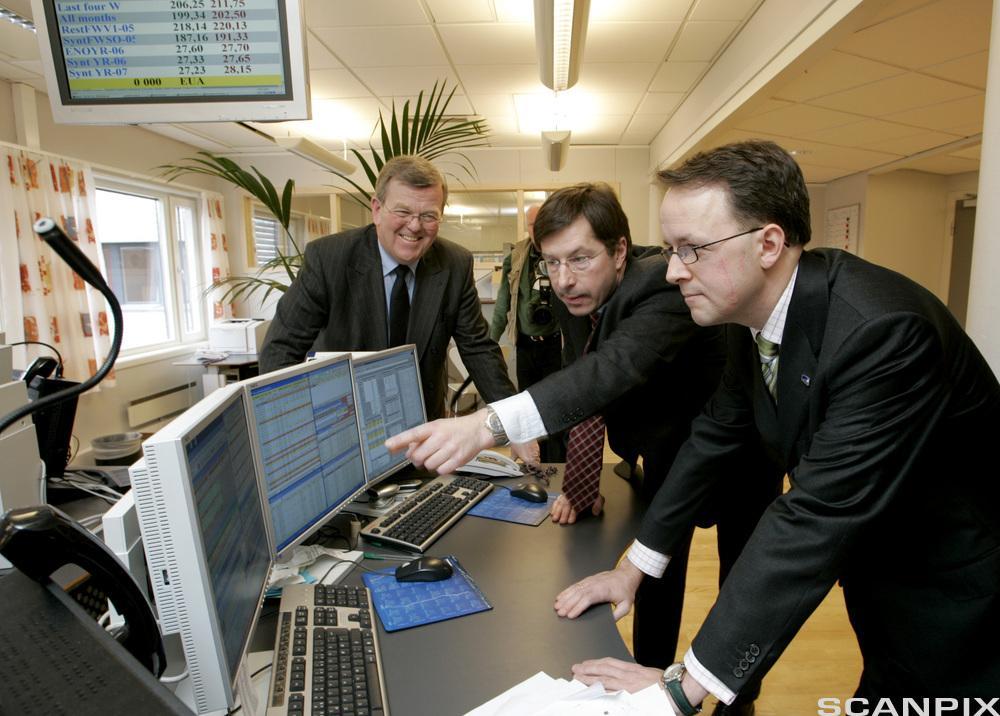 Tre personer står ved dataskjermer.