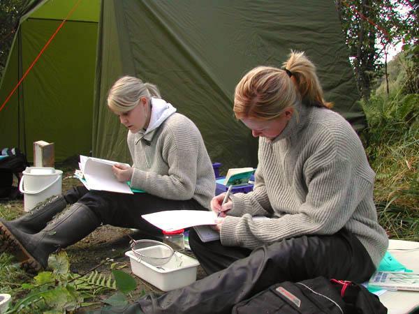 To jenter skriver notater under feltarbeidet. Foto.