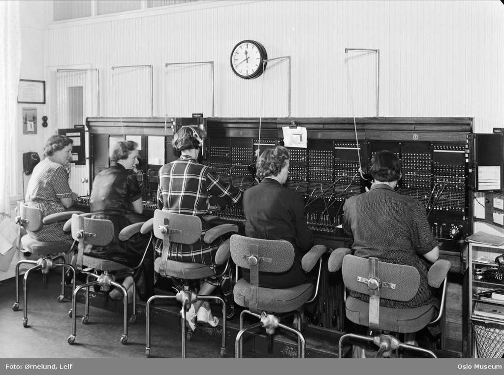 Kvinner sitter ved et stort svitsjebord der de kobler sammen abonnenter som ønsker å ringe hverandre. Foto.