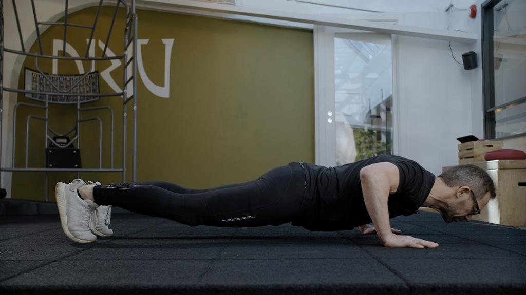 En person står med tærne og hendene i gulvet, han har helt strak kropp. Foto.
