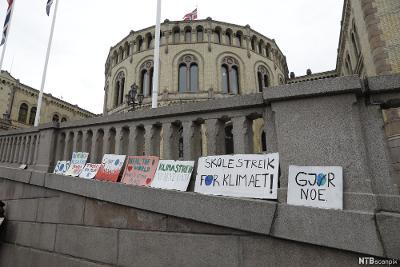 Plakater med paroler for klimaet satt opp foran Stortinget. Foto.