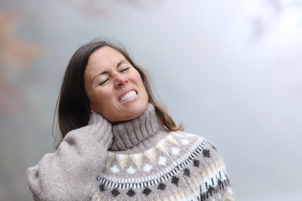 Kvinne skjærer grimase og tar seg til nakken. Foto.
