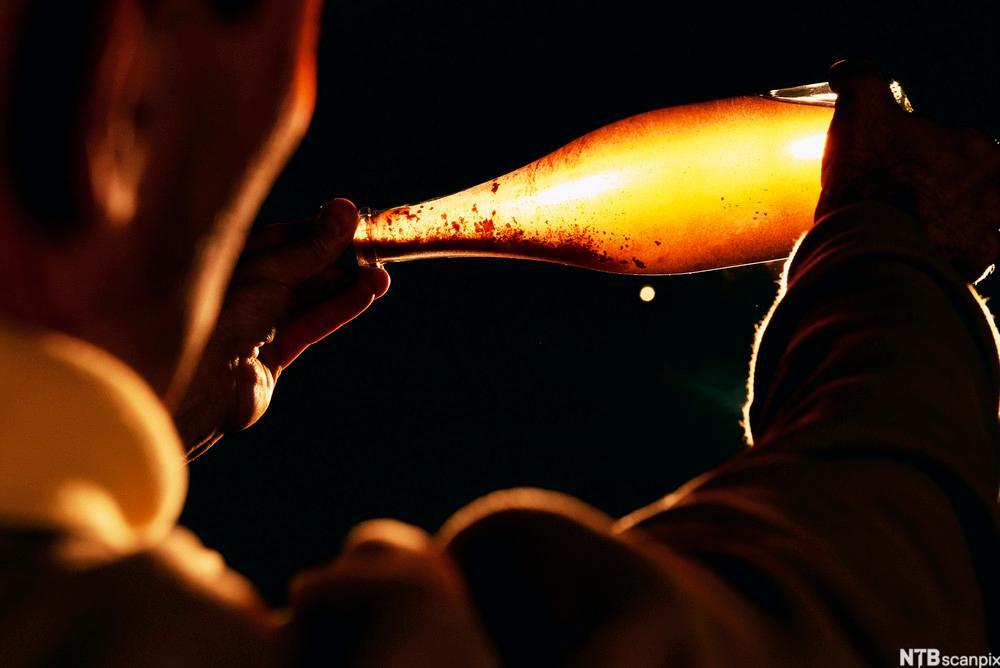 Erick de Sousa sjekker en flaske champagne. Foto.