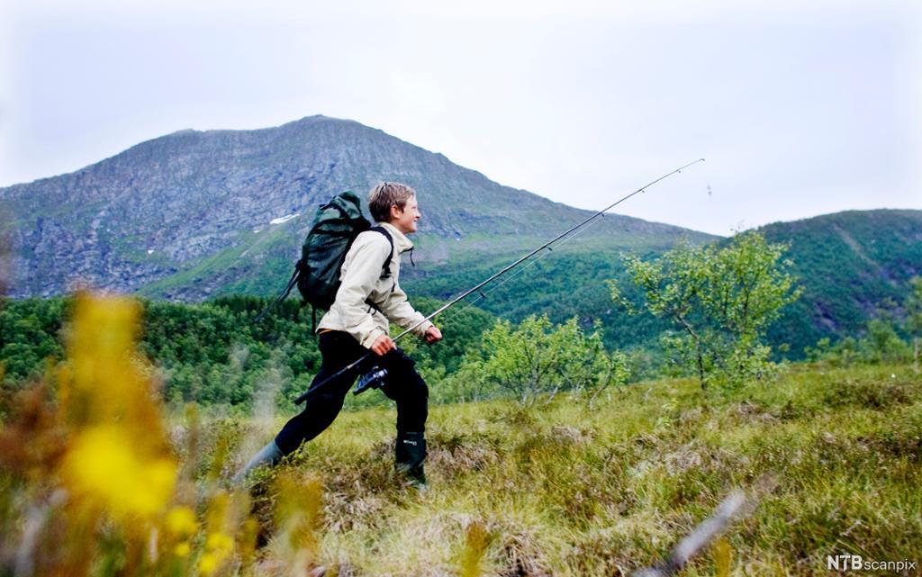 Ungdom på tur i myra med sekk og fiskestang. Foto.