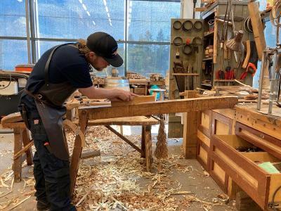 Mann jobber med trearbeid i verksted. Foto.