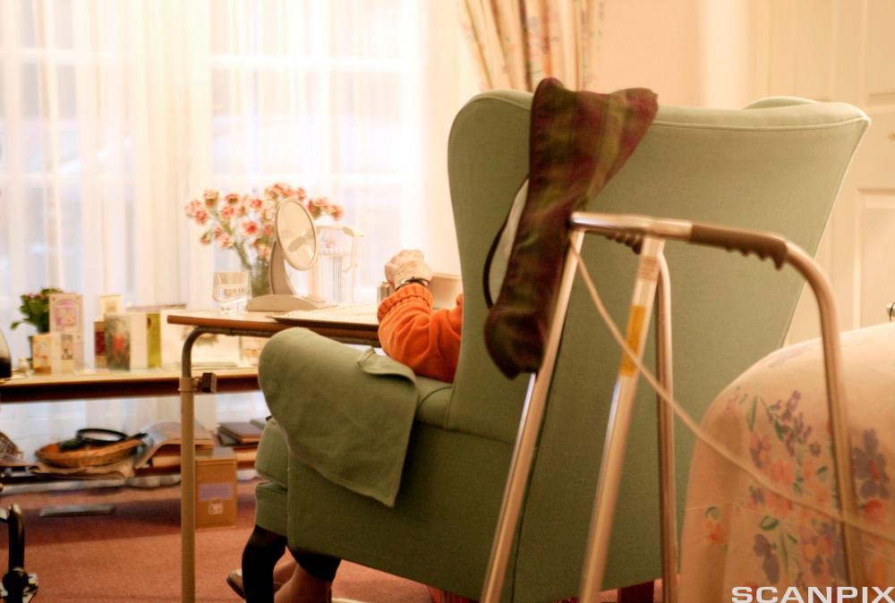 Kvinne i stol med rullator ved siden av seg. Foto.