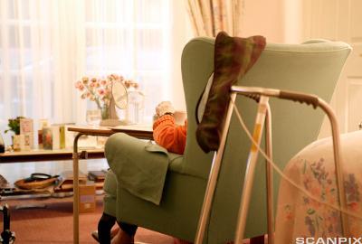 en eldre person sittende i en lenestol med ryggen til. Foto.