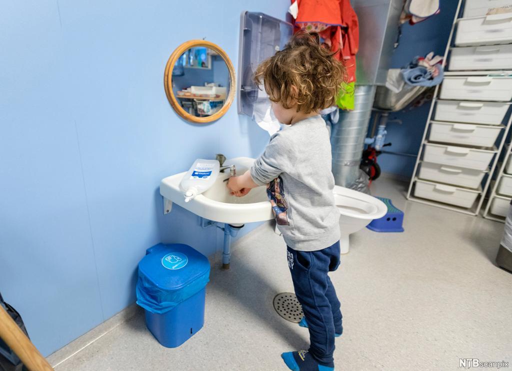 Et barn vasker hendene etter et dobesøk i barnehagen. Foto.