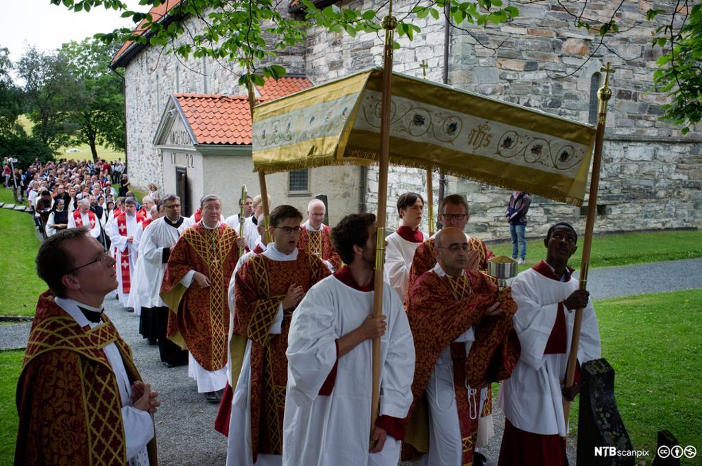Menn med hvite kjortler og røde vester bærer en baldakin i en proesjon. I bakgrunnen en kirke. Foto.