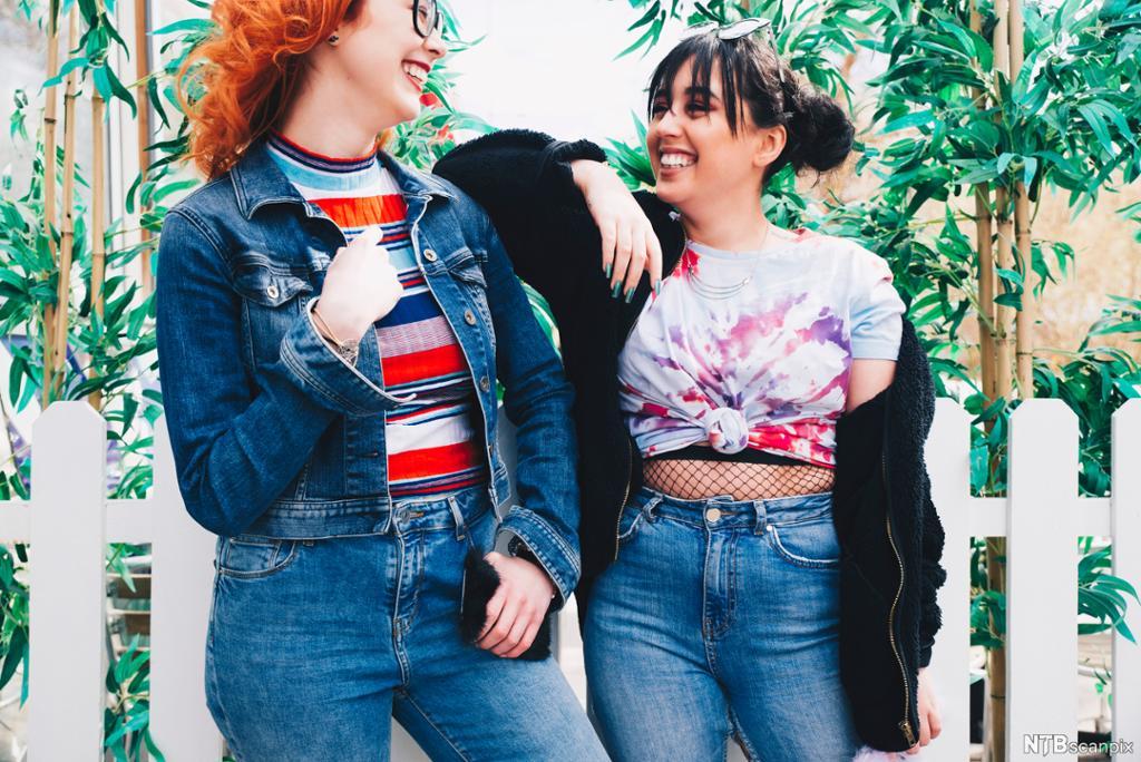 To unge smilende kvinner foran et gjerde og planter. Foto.