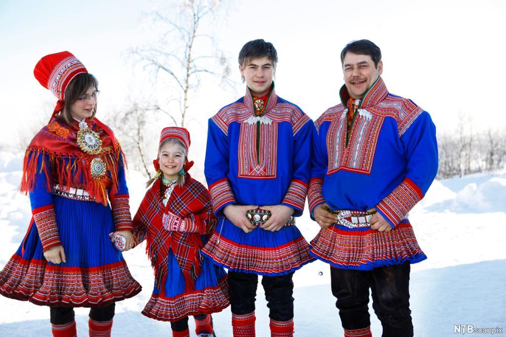 Samisk familie med samekofter på. Foto.