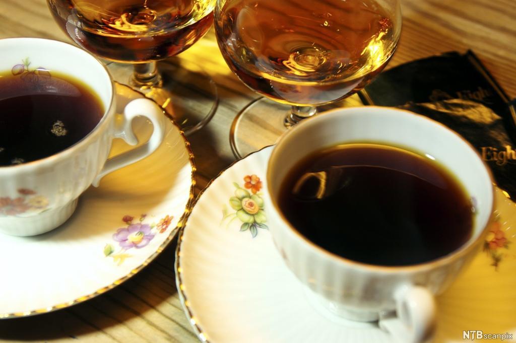 To pene kaffekopper med kaffe og to konjakkglass med konjakk som står ved siden av hverandre på et bord. Foto.