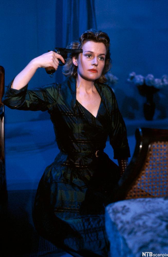 Bilde av skuespiller Catherine Wilkin i rollen som Hedda Gabler. Hedda er kledd i sort og holder en pistol mot tinningen sin.