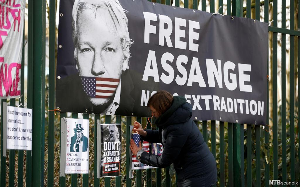 """En kvinne fester en stor plakat på gjerdet utenfor rettssalen The Old Bailey i London. Plakaten viser ansiktet til Julian Assange. Munnen hans er kneblet med en teip i fargene til det amerikanske flagget. Tittelen på plakaten er """"Free Assange"""". Foto."""