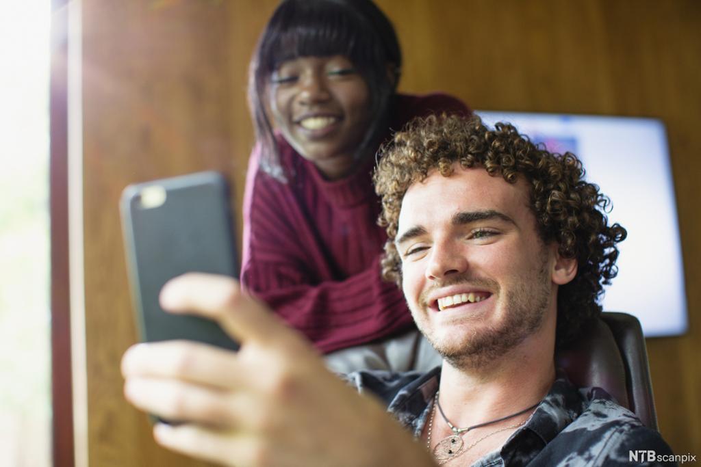 En ung mann og en en ung dame ser på en mobil og ler. Foto.