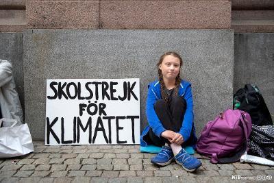 """Greta Thunberg sittende utenfor det svenske parlamentet. Til venstre for henne står en plakat med teksten """"Skolstrejk för klimatet"""". Til høyre er en lilla og en sort skolesekk og et pledd. Bildet er tatt i august 2018. Foto."""