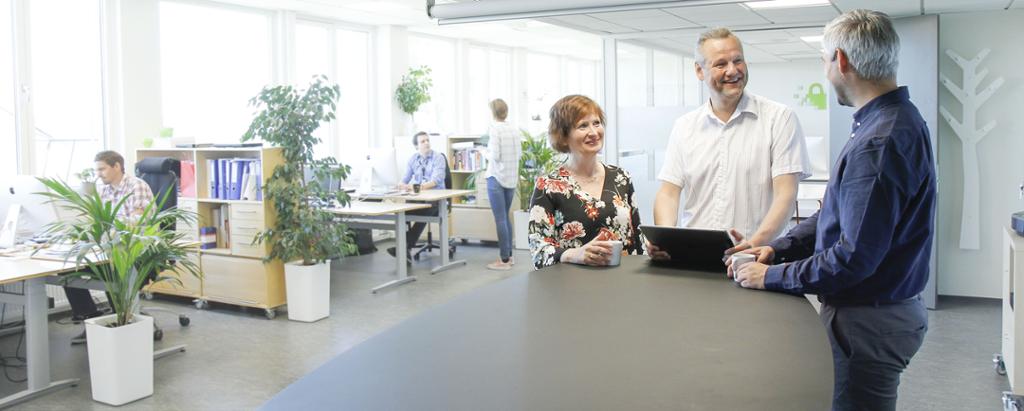 Tre ansatte ved NorSIS står og har et uformelt møte. Foto