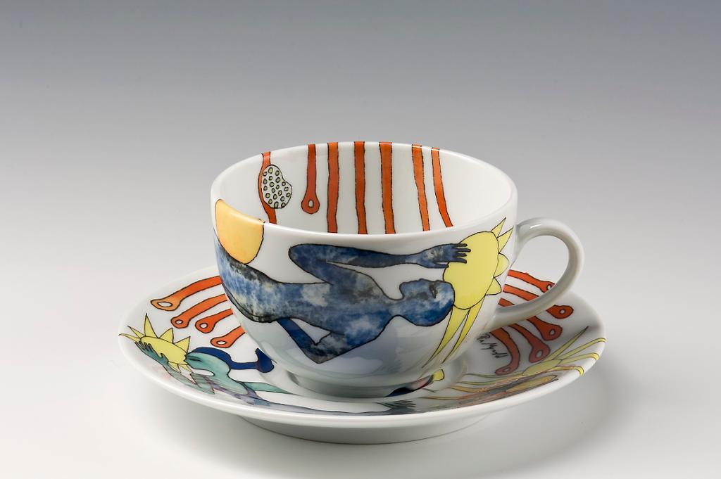 Kopp med skål i porselen med trykket dekor. Foto.