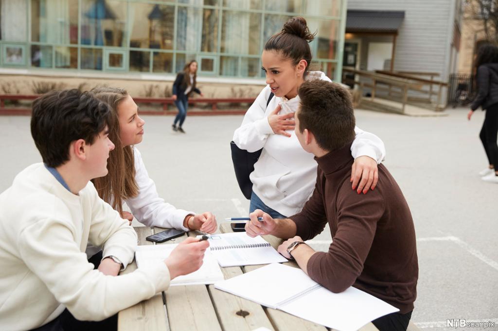 fire ungdommer snakker rundt et bord