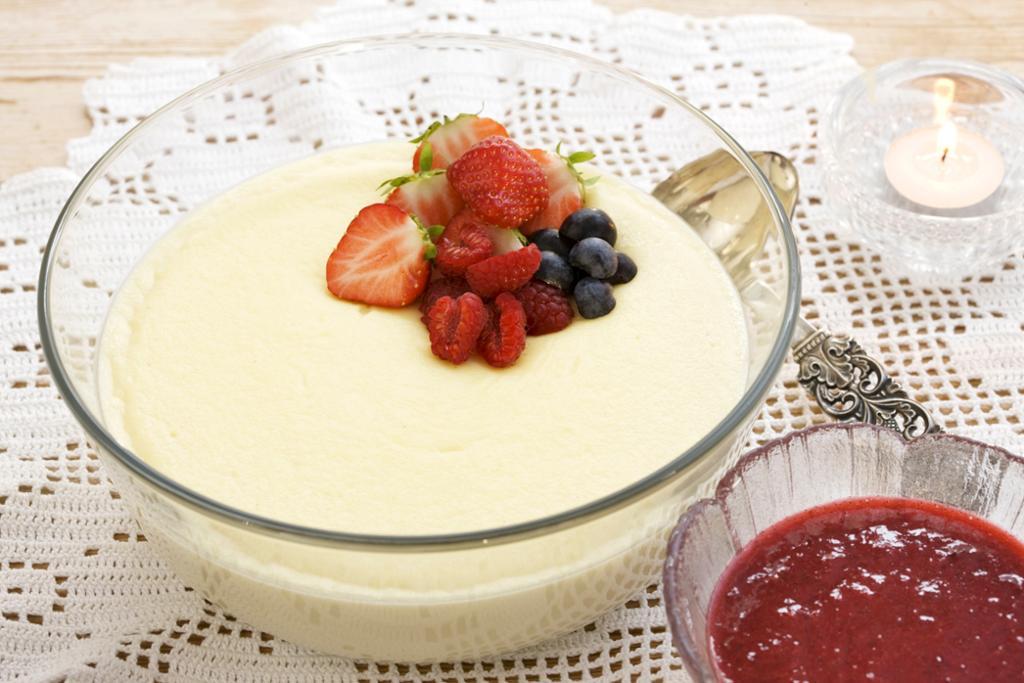 Fløterand i en serveringsbolle, pyntet med jordbær, bringebær og blåbær. Rød saus servert i skål ved siden av. Foto.
