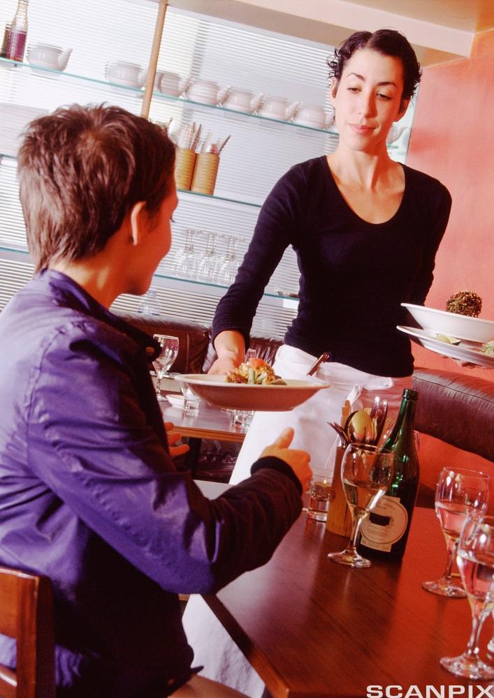 Ein servitør serverer ein kunde. Foto.