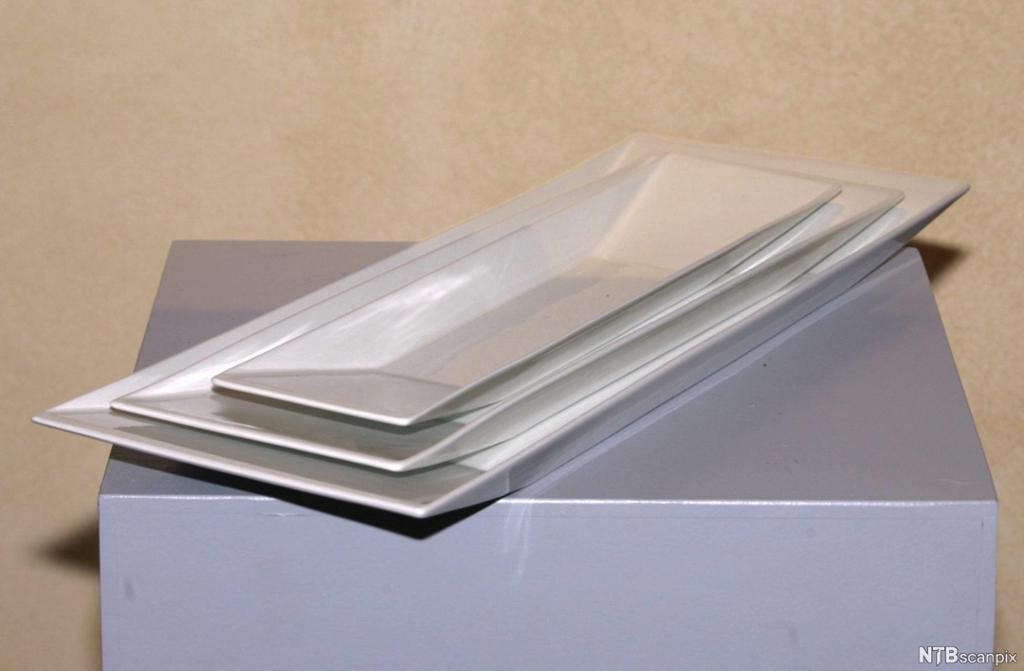 Tre avlange og firkantede hvite porselensfat. Foto.