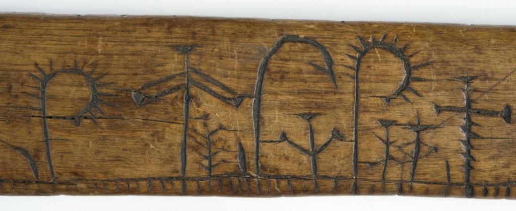 Nærbilde av symboler på en primstav. Foto.