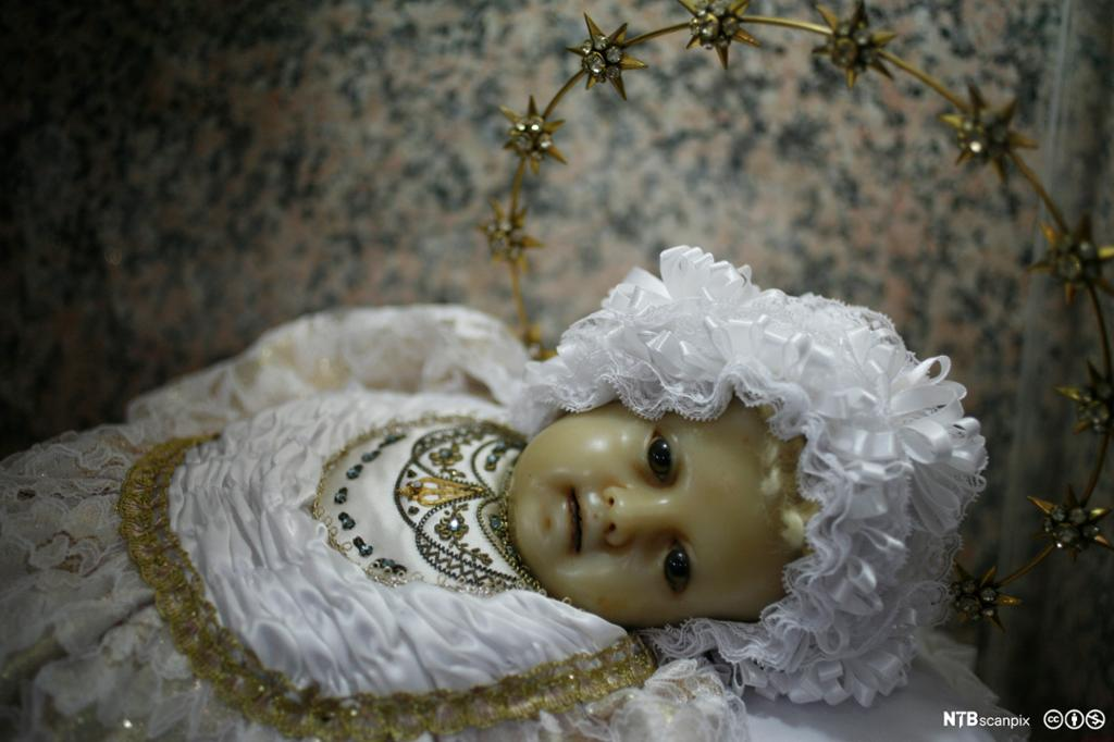 Dukke kledd i hvit kjole og kyse med glorie. Foto.