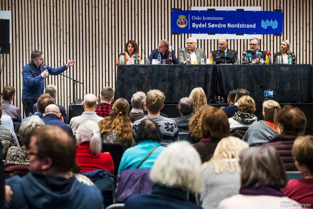 Politi og nasjonale og lokale politikere på podiet under et folkemøte. Publikummere sitter i salen. Foto.
