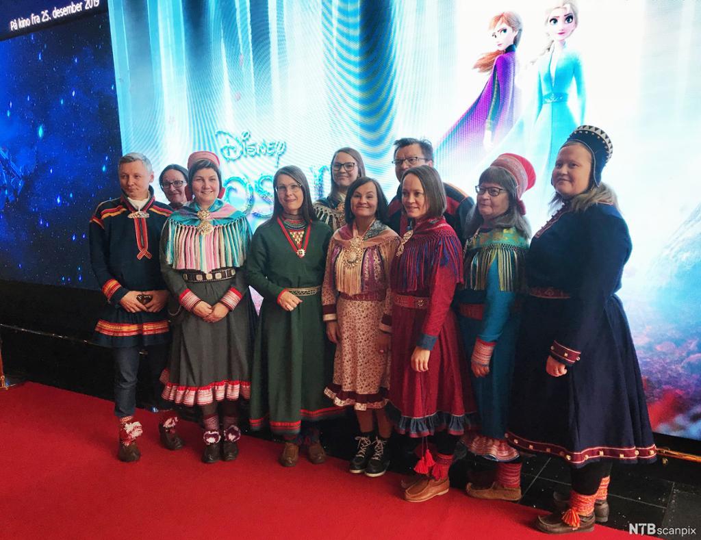 Flere mennesker kledd i tradisjonelle samiske drakter på rød løper. I bakgrunnen er et bilde fra Disneyfilmen Frost 2. Foto.