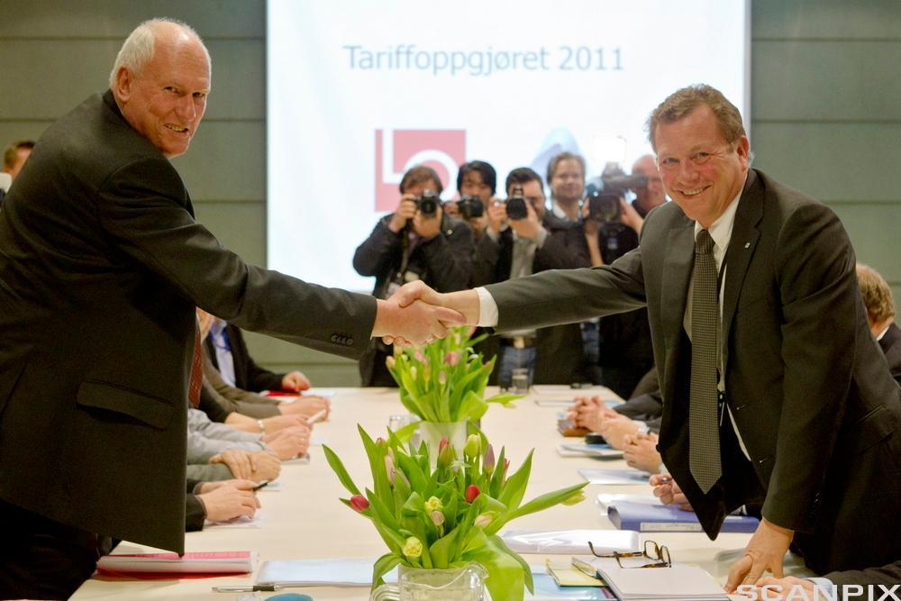 To menn som gir hverandre håndtrykk over et bord. Foto