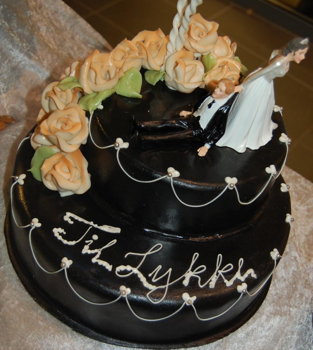 En bryllupskake med svart marsipan og roser. Foto.