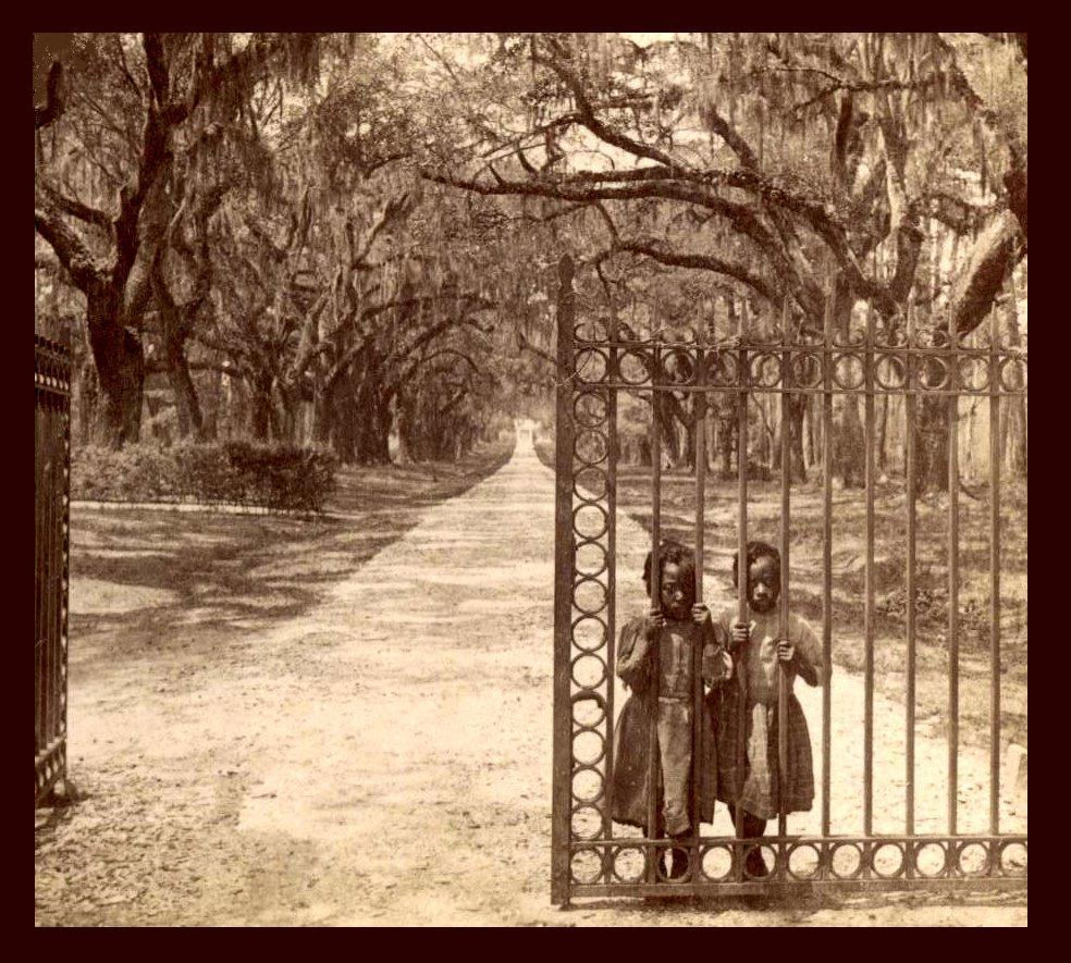 Two girls standing behind a barred gate. Photo.