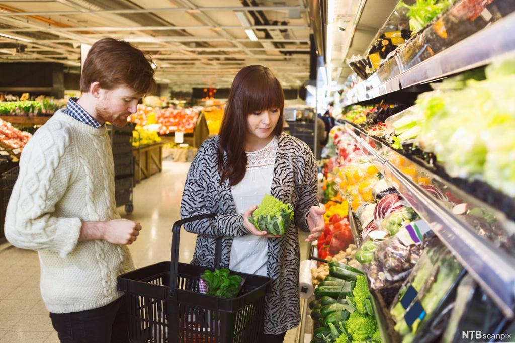 Ung mann og ung kvinne studerer grønnsaker i butikken. Foto.