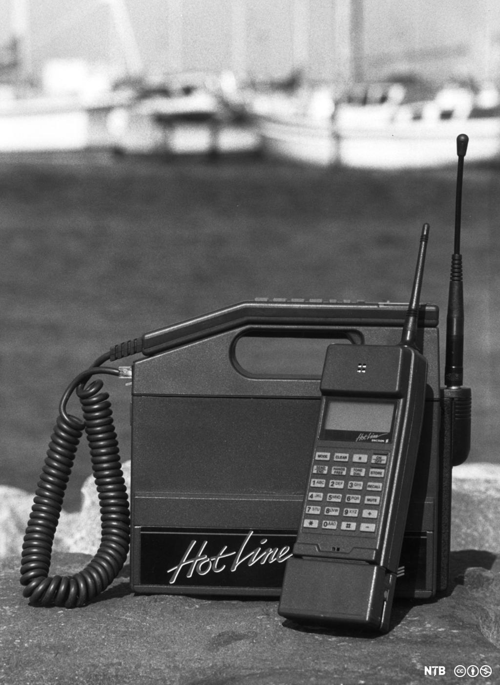 En gammel mobiltelefon formet som en boks med bærehåndtak. Foto.
