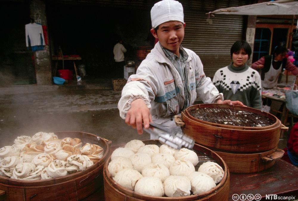Ung mann damper og selger dumplings. Foto.