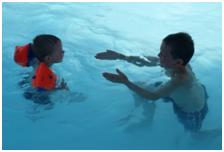 Barn i basseng med armringer og en voksen. Foto.