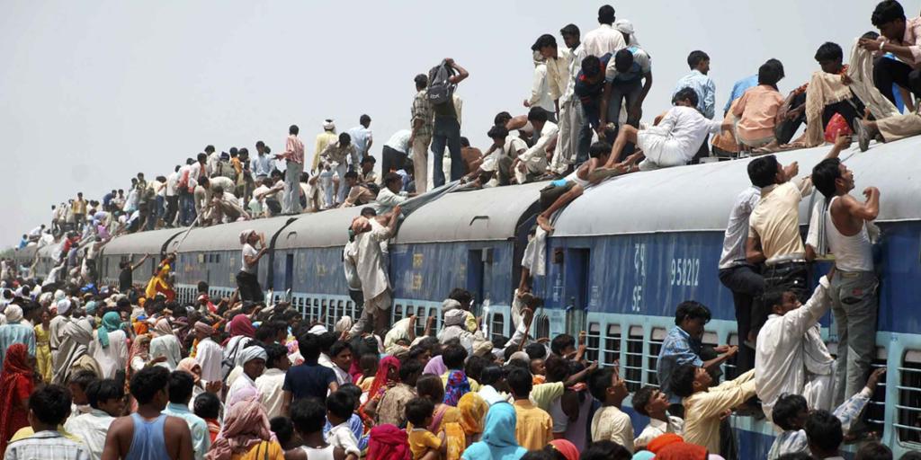 Folkemengde i Asia klatrer opp på taket på et overfylt tog.  Foto.