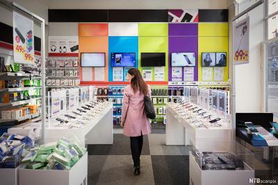Kvinnelig kunde kikker på mobiltelefoner i en elektronikkforretning. Foto.