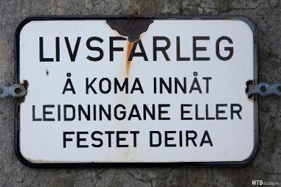 Eldre emaljeskilt med åtvaring på nynorsk. Foto.
