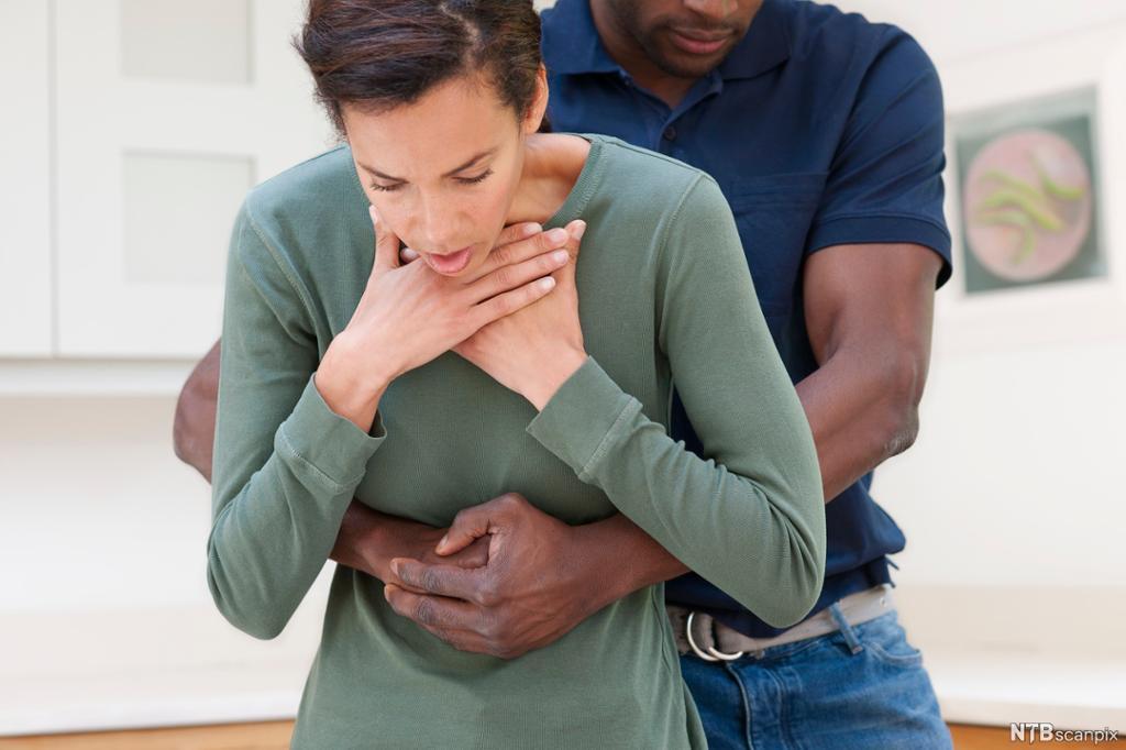 En kvinne holder seg til halsen. En mann står bak  henne med hendene under brystet hennes og gjør Heimlichs manøver. Foto.