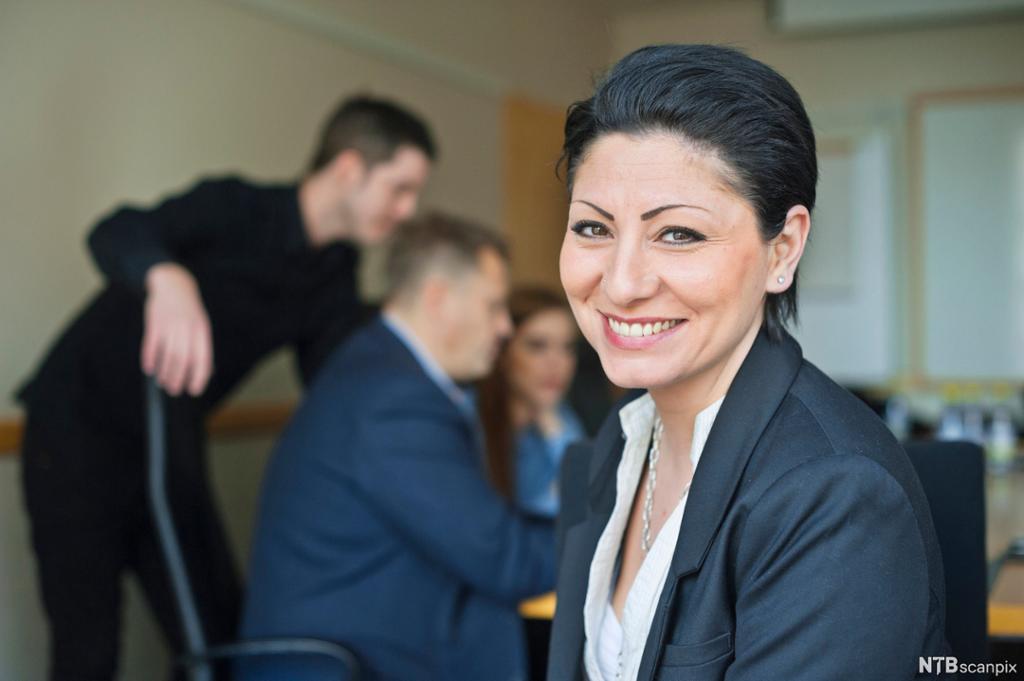 En forretningskvinne sittende foran flere medarbeidere i et møte. Foto.