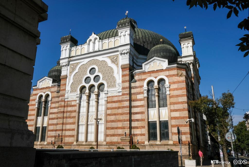 Fasade på bygning med kuppelformet tak. Utsmykket med søyler, buer og ornamentikk. Foto.